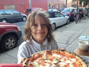 Jacob outside with pizza at Nomad Pizza Company