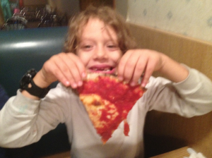 Jacob with a slice of Tacconelli's pizza